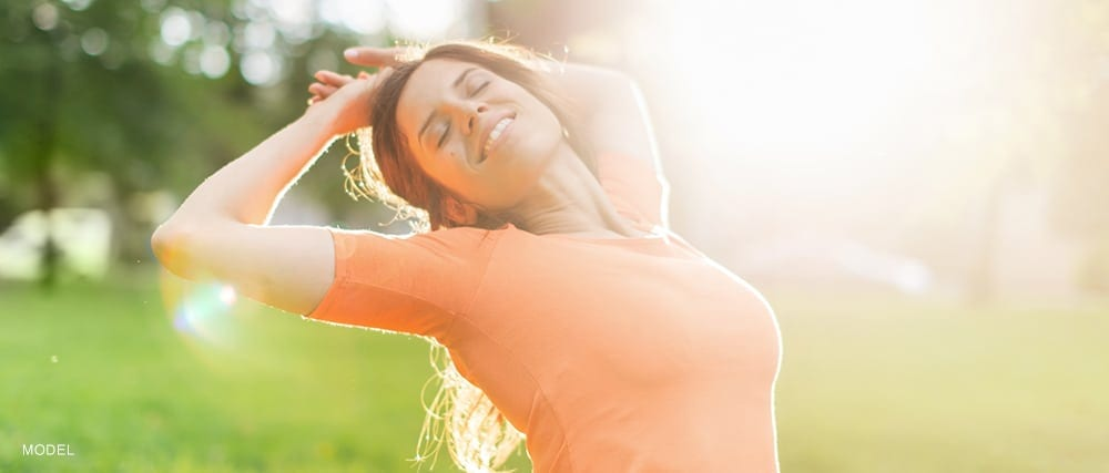 Model Stretching Arms Towards Head With Eyes Closed Basking In Sunlight