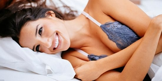 Model Lying On White Bed Sheets In Blue Lace Night Blouse