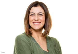 Middle Aged Female With Short Brown Hair Smiling Wearing Green Sweater Blouse